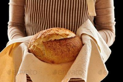 Baker holding loaf of homemade bread