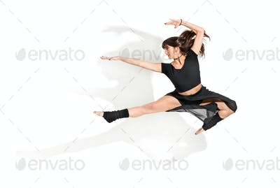 Agile young woman dancer performing a front half split jump