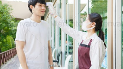 Asia female restaurant staff wearing protective face mask using infrared thermometer.