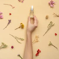 Face serum on beige floral background above.