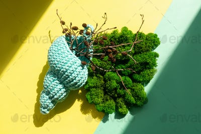 Knitted shell with moss and branch decorating.