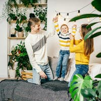 Happy family in bedroom, yellow gray colors.
