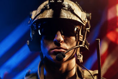 Portrait of special forces soldier in glasses and helmet against US national flag