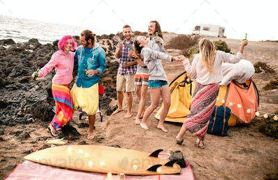 Hipster friends having fun together at beach party on camping time