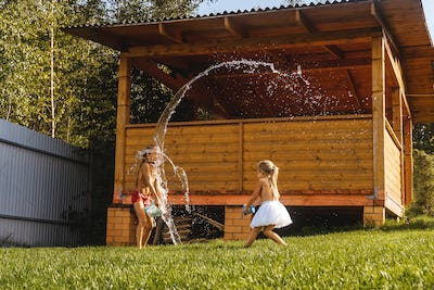 Happy kids playing with water in garden
