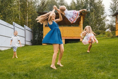Happy kids and mother playing in garden