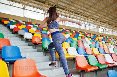 Active young woman running up on stairs in the stadium.
