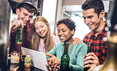 Multiracial friends drinking beer and having fun with tablet at cocktail restaurant