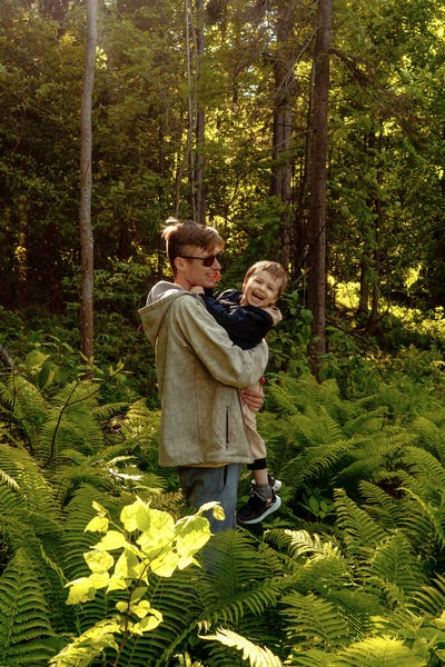 Father and son in forest.