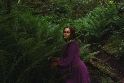 The young girl in fern forest.