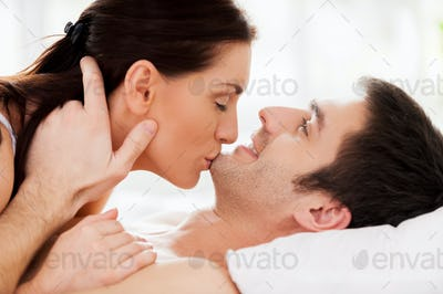Sensual moments. Beautiful young loving couple lying in bed while woman kissing her boyfriend chin