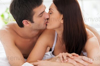 Loving couple kissing in bed. Beautiful young loving couple lying in bed and kissing