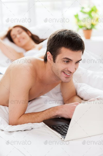 Surfing web in bed. Cheerful young man using laptop while lying in bed with his girlfriend