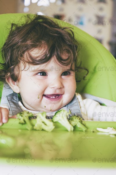 Baby eating food in her green highchair