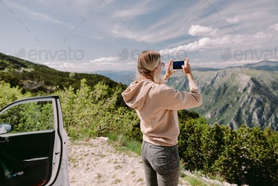 pretty woman travel by car and using smartphone on road trip vacations