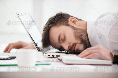 Sleeping at working place. Young man in formalwear sleeping at the working place