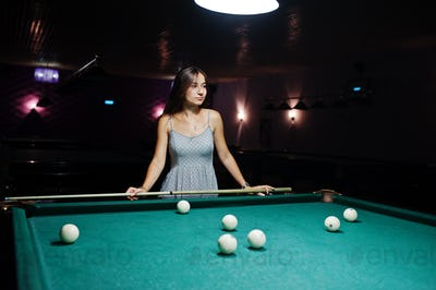 Portrait of an attractive young woman in dress playing pool.