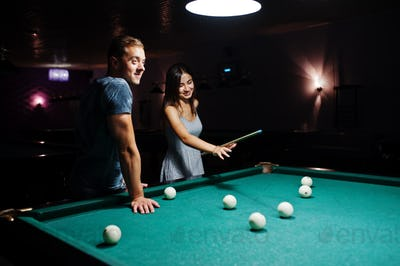 Woman in dress playing pool with a man in a pub.