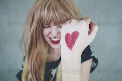 Strong woman with a red heart drawing in her hand