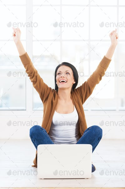 Successful young woman. Female student with a laptop cheering in success