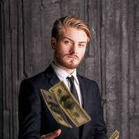Rich and successful. Handsome young man in formalwear throwing money and looking at camera