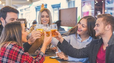 Group of people hanging with each other in a bar and cheering with beer