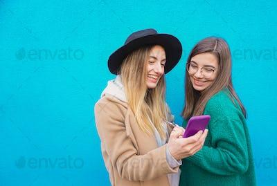Girls in a blu background taking selfie