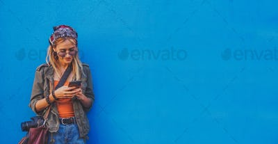 Young girl standing by the blue background holding a smartphone