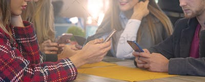 Friends sitting in bar and using smartphone