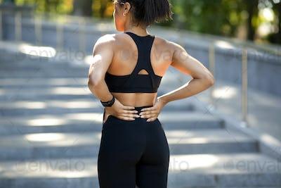 Black woman having lower back pain, got hurt during exercising
