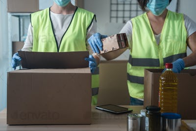 Female warehouse coworkers preparing food delivery boxes while wearing safety mask