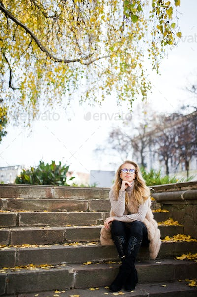 Blonde girl at fur coat and glasses sitting on stairs with yellow leaves.