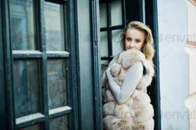 Blonde girl at fur coat posed against old wooden door.