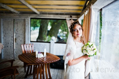 Charming bride at wedding bouquet at her hands near window at cafe
