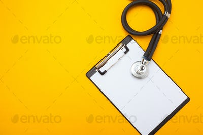 Flat lay design of stethoscope and blank clipboard pad with for medical concept