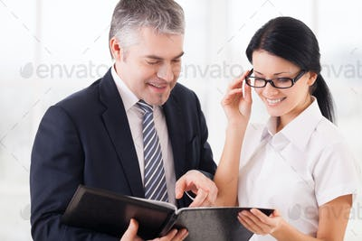Business people at work. Two smiling business people holding note pad and smiling