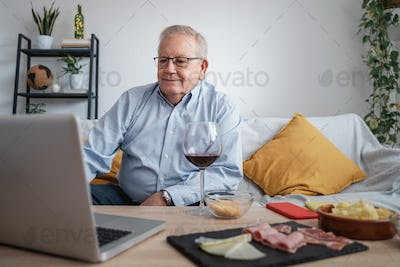 Happy senior man having video call with laptop computer at home during lockdown isolation