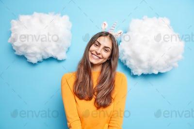 Lovely charming woman with long dark hair tilts head smiles gently wears unicorn headband long sleev