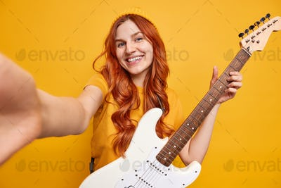 Cheerful ginger teenage girl stretches arm for making selfie smiles gladfully with teeth glad to buy