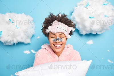 Happy curly Afro American woman gets rid of black dotes on nose using special patch wants to have fl