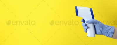 Hand in glove hold thermometer gun on yellow background