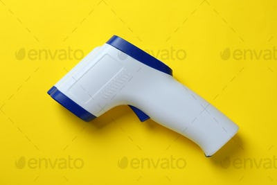 Thermometer gun on yellow background, close up
