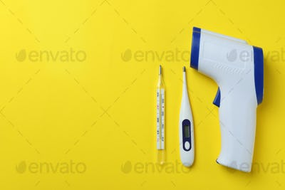 Different thermometers on yellow background, space for text