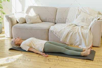 Calm retired woman practicing Savasana or Corpse Pose while lying on yoga mat in living room at home