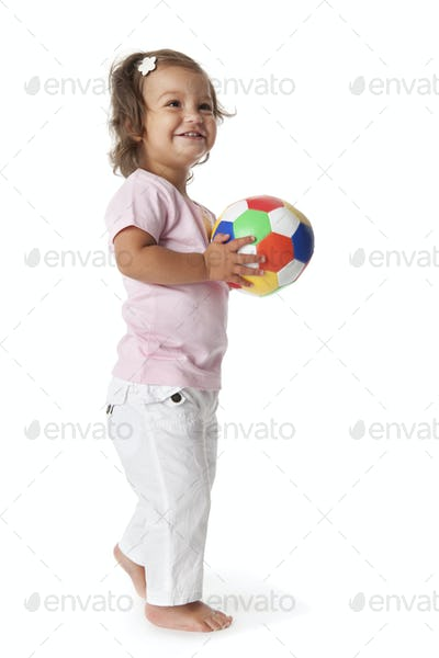 Toddler girl playing with a colored ball