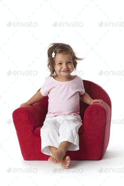 Toddler girl making fun in an armchair