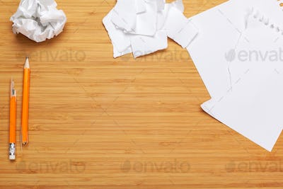 White note pad on a wooden table. Around the notepads lies lot crumpled paper