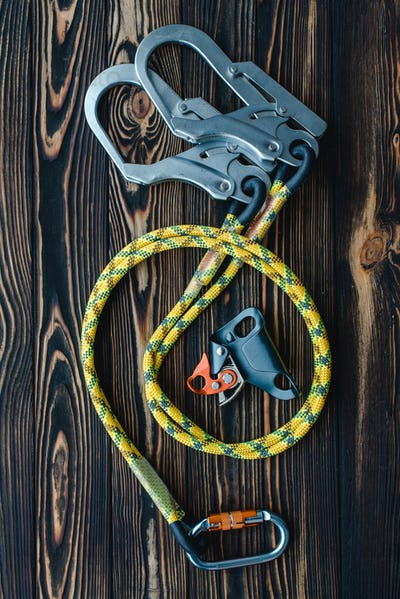 Isolated photo of climbing equipment. Parts of carabiners lying on the wooden table