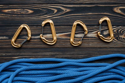 Isolated photo of climbing equipment. Part of carabiner lying on the wooden table