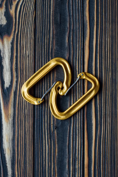 Good lighting. Isolated photo of climbing equipment. Parts of carabiners lying on the wooden table